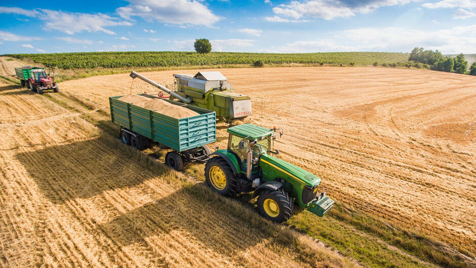 Combine Harvester Pouring Grain into Trailer Towed by Tractor